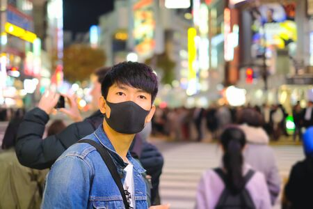 Portrait of young asian man with black protective face mask and travel in Shibuya, Japan at night