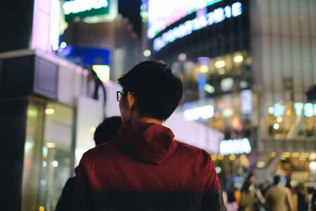 Young man walking in front of department store in big city with bokeh light background at night Banco de Imagens