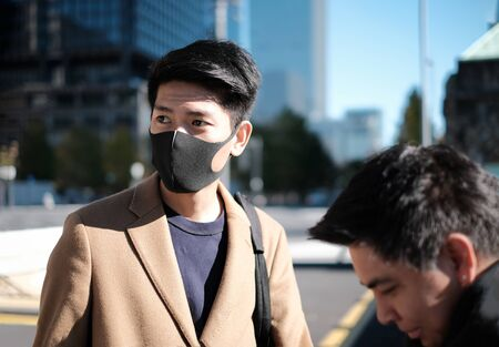 Young asian man wear protective face mask and looking for the place to travel Banco de Imagens