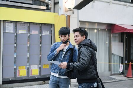 Two young asian man travel in the city and searching the way to visit the famous place
