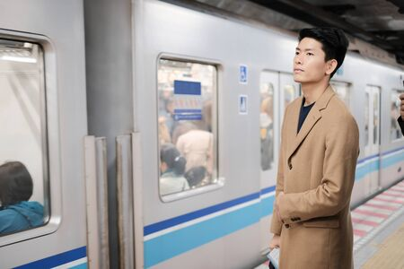 Portrait of young asian man waiting for the train and go to next station Banco de Imagens