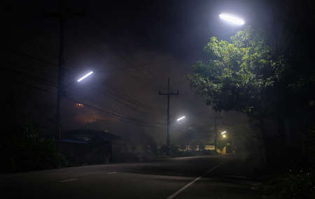 Empty road underneath street light with smoke at night and UFO on background Banque d'images