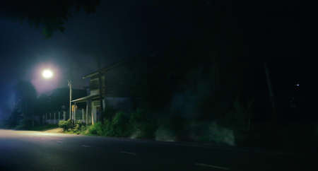 Old wooden house and smoke at night . Horror scene