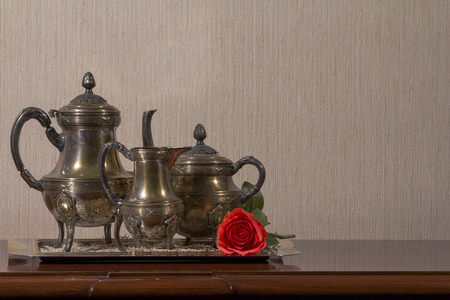 A silver tea set and red rose on a wooden desk on left side photo