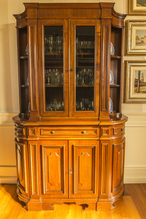 designates: antique wooden furniture full of precious glasses