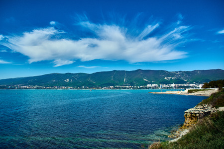 Sea bay with clear turquoise water and cumulus clouds in the sky
