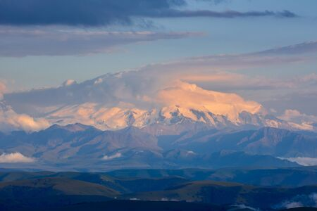 Elbrus at sunset. Elbrus at sunset is covered with a hat of clouds. Stock Photo