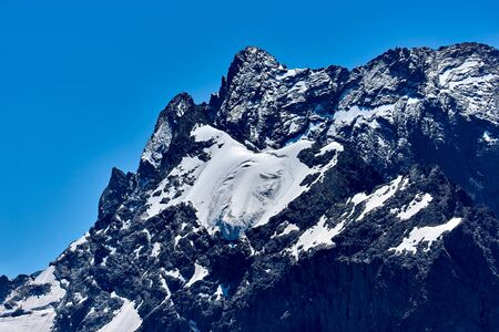Mountain peak in black, covered with glaciers and snow. Dombay, North Caucasus, Russia Stock Photo