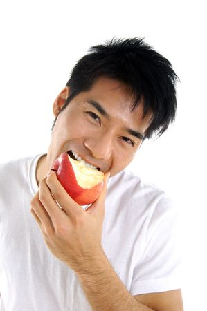 Young Asian man eating red apple close up
