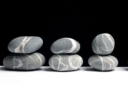 row of Stack of zen stones on black photo