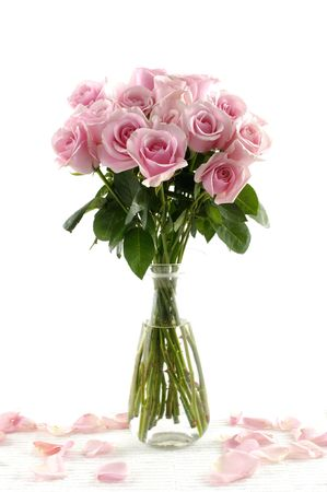 Bouquet of pink roses in glass vase with petals isolated on white Stock Photo