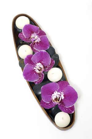 Bowl of beauty orchid with candle, stones photo