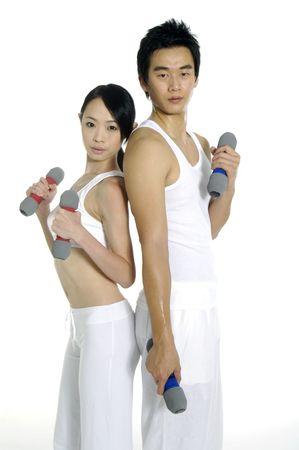 Couple (male  female) lifting dumbbells on white