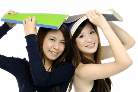 Pretty asain smiling and holding book on head Stock Photo