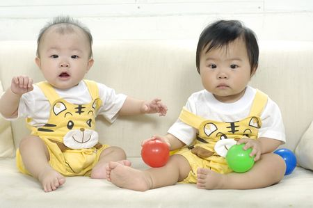 Small two asian children looking up on sofa photo