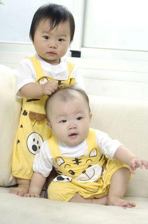 hermanos jugando: dos ni�os asi�tico en sof�