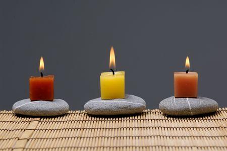 alight: Riga di candela aluce colorata su pietre zen