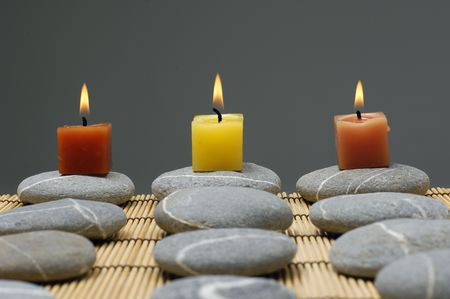alight: Colorful alight candle on row of stones Stock Photo