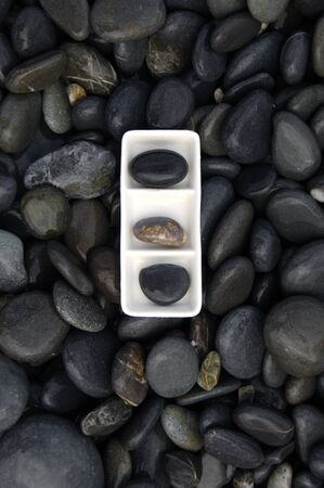 Plate of three striped stone on black stones photo