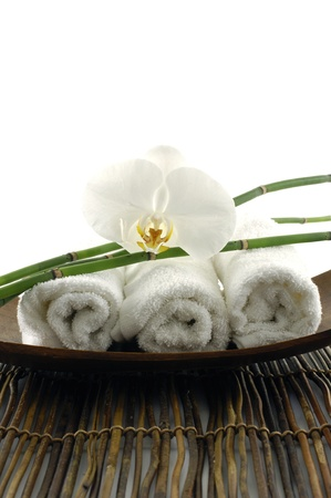 Bowl of towel and orchid on mat photo