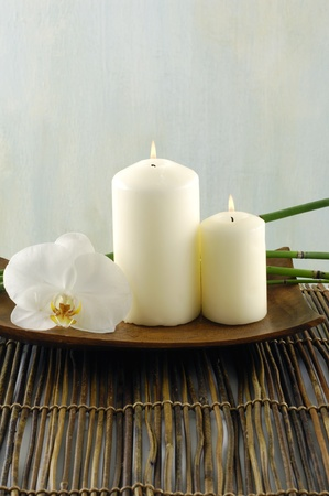 Bowl of candle and orchid on mat photo
