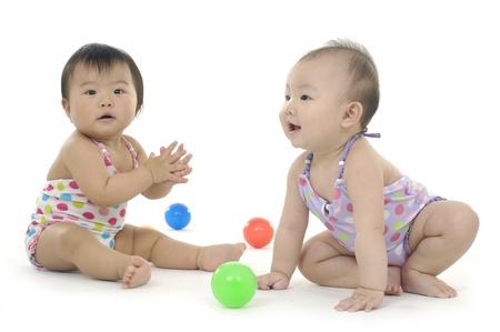 hermanos jugando: dos ni�os asi�ticos jugar a la pelota de colores Foto de archivo