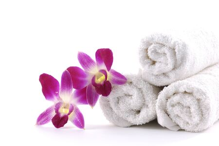 White rolled up towel with pink orchid photo