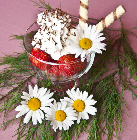 Strawberries with beaten cream topped with grated chocolate in a glass with flowers photo