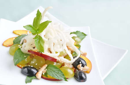light salad with chicken, grapes, nectarines, sesame, with lemon dressing, decorated with fried rice noodles with mint photo