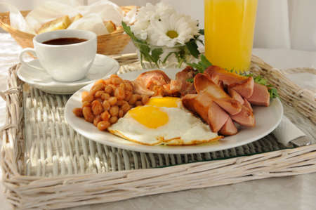 Breakfast with scrambled eggs, bacon, sausage and beans photo