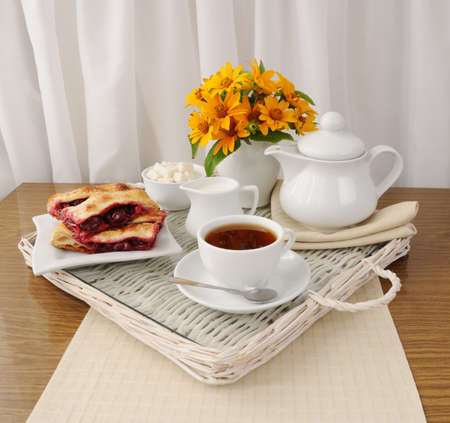 Breakfast with the cherry strudel with tea and milk on a tray photo