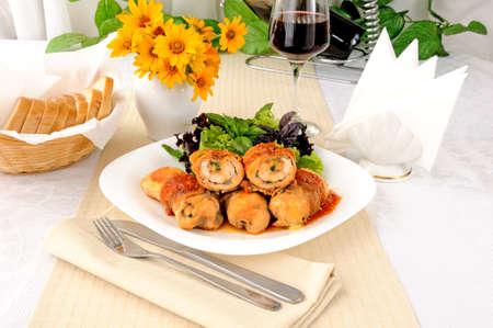 carnes y verduras: Pollo rollos de queso, envueltos en tocino y hierbas en salsa de tomate y ajo Foto de archivo
