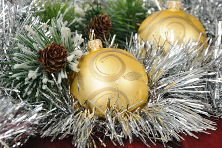 seasonally: Christmas balls against the backdrop of tinsel with pine branches and cones