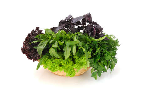 Basket with fresh herbs: basil, lettuce, parsley and arugula isolated photo