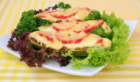 Stuffed zucchini with a mixture of vegetables with tomato and cheese with herbs photo