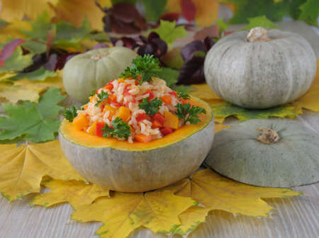 Rice with pumpkin and vegetables in a bowl of pumpkin in the background of autumn leaves photo