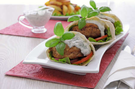 Patty in pita bread with vegetables in cream sauce photo