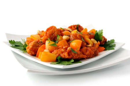 Pork in batter with pineapple and bell pepper in sweet and sour sauce with peanuts Standard-Bild