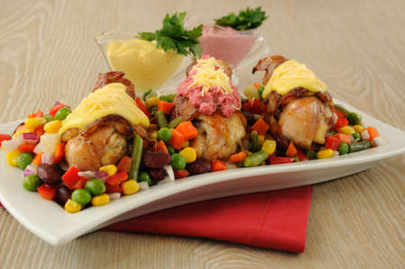 roast chicken leg wrapped in bacon with vegetables and two different sauces photo