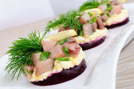 Appetizer of herring with onions on the beets and eggs, lemon and dill Stock Photo - 11880763