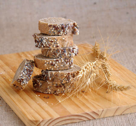 A stack of slices of bread with grains on a wooden board with ears of wheat  photo
