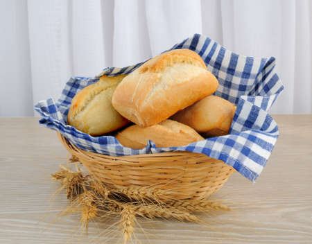 Fresh bread in a basket with a cloth cover ears of wheat Standard-Bild