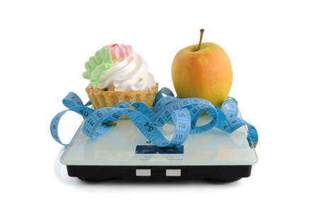 The dilemma of cake or an apple wrapped in the centimeter scale on white background (isolated) Stock Photo