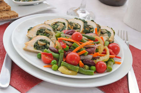 Sliced chicken roll with spinach and mushrooms garnished with vegetables photo