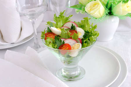 Frize salad with cherry tomatoes, radish and quail eggs photo