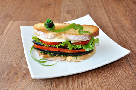 Sandwich with eggplant, tomatoes, peppers and cheese photo