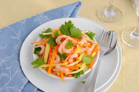 Salad of celery root and leaves with carrots, apples and shrimp photo