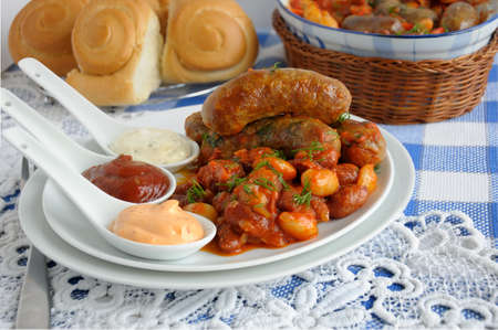 Home sausage with beans, onions and carrots in a tomato sauce Standard-Bild