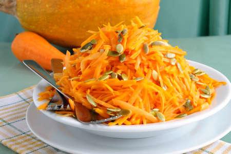 Salad of fresh pumpkin and carrot with pumpkin seeds photo