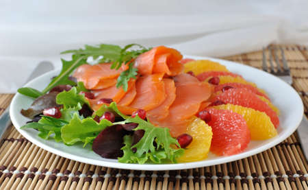 Appetizer of salmon with orange and grapefruit and a mixture of lettuce photo